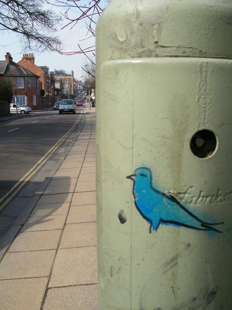 Blue bird graffiti on a light post box in Winchester