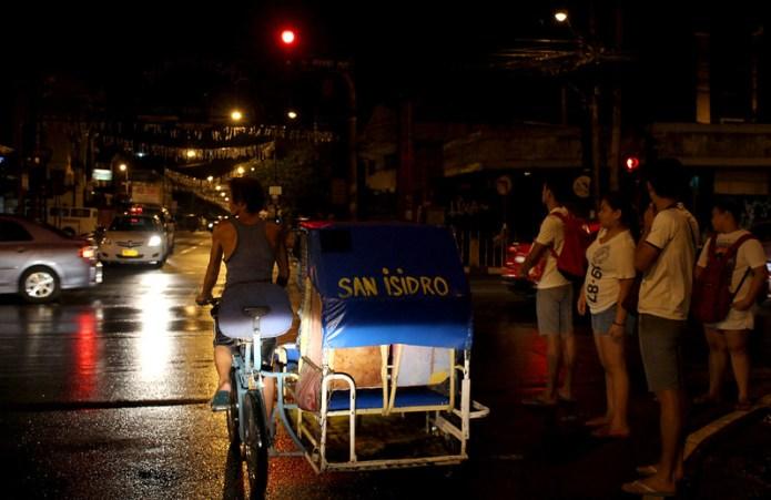 pedicab on rainy street at night