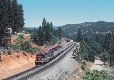 SP 9346 with Amtrak Train 5, the San Francisco Zephyr, coming into Colfax, CA.  Shot from HWY 174 bridge. The dirt road in the lower right is the ROW of the Nevada Co. Narrow Guage,  in August 1980
