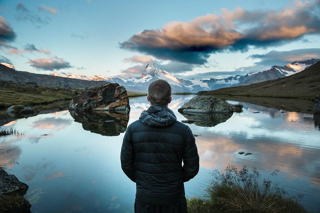 Imagen gratis de un chico frente a un lago y montañas