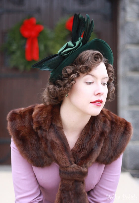 A giant feathered green New York Creations hat paired with a vintage fur collar and purple suit for a festive look