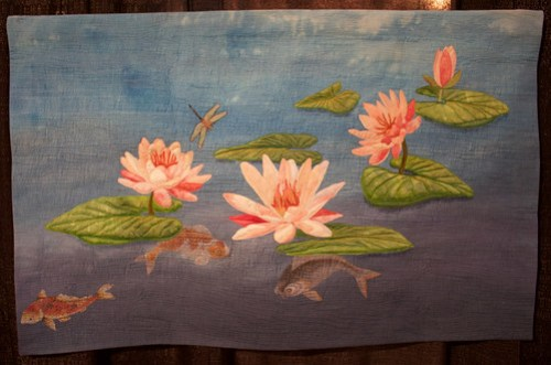photo of an art quilt featuring lotus flowers and koi fish