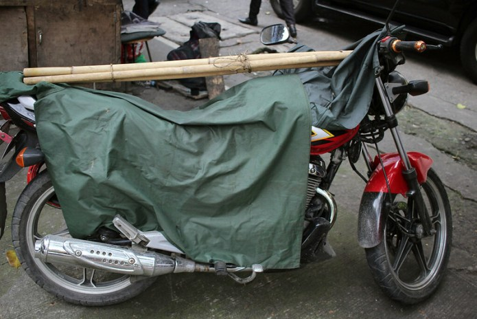 bamboo on top of a motorcycle covered with a tarp