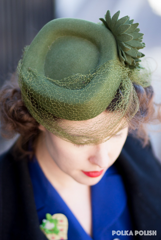 A green 1940s tilt hat featuring a sweep of veiling and cut-felt flowers along one side