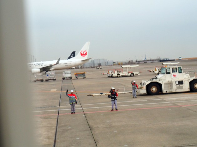 JAL機を見送る人