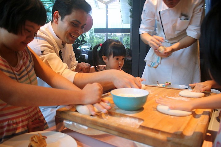 Chefs showing kids how to make pizza
