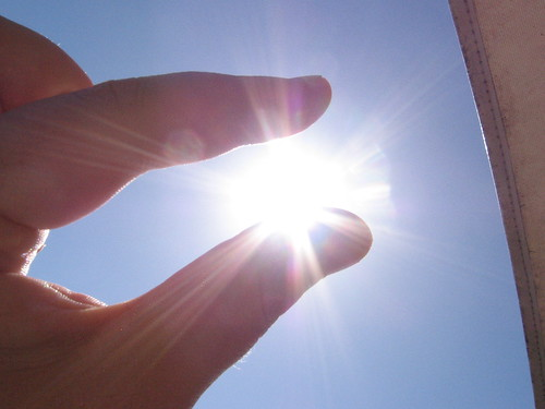 A hand is held up against a blue sky so that the thumb and index finger appear to hold the Sun.