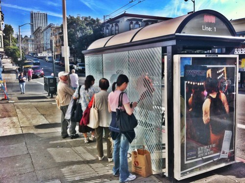 It's so HOT in San Francisco right now! People using the back of the Muni shelters for shade.