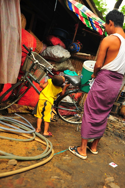 Myanmar strength training: 4 year old boy tries to hold up bike as father looks on.