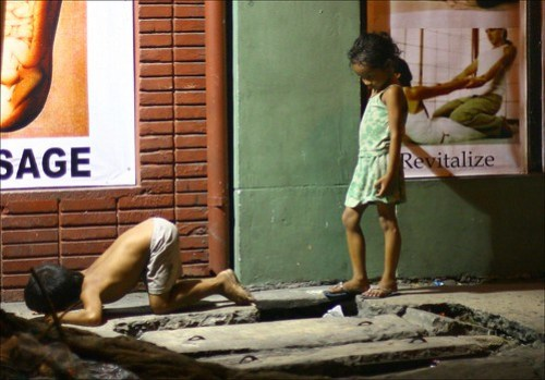 street kids in front of a foot massage ad