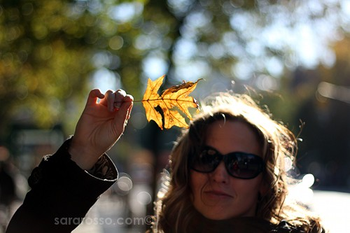 A woman holding a fall leaf in New York City