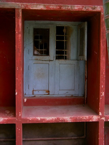 A white window set into a red wall.