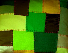 little green quilted pillow with orange stitching