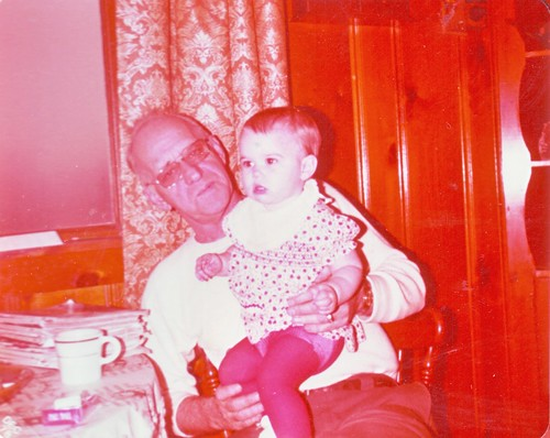 A older balding white man with glasses holds a toddler-age girl in a polka dotted dress