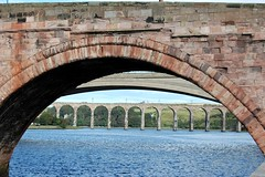 Looking through the arch of one bridge to see the bottom of the arch of another bridge, and in the distance the broad span of yet another bridge