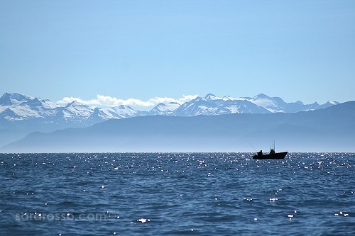 Fishing all alone with snow-covered mountains in the distance, in Alaska