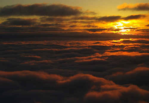 Sun and layered nimbus clouds at dusk from the air