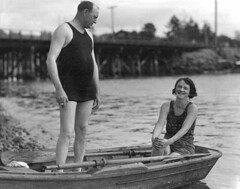 Man and woman in bathing suits in a rowboat ne...