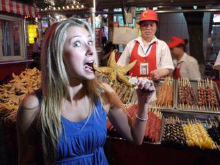Julia Dimon eating starfish at Donghuamen Night Market Beijing