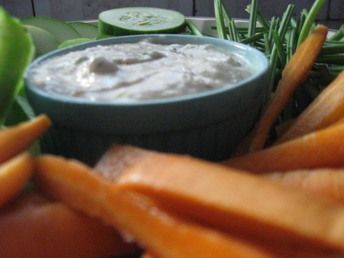 Roasted onion dip peaking out from a forest of veggies
