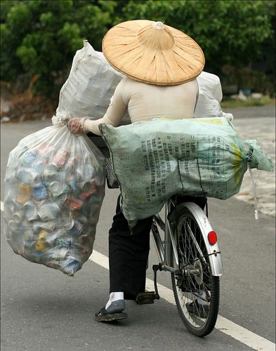 farmer in a straw hat carrying sacks of empty cans on a bike 1