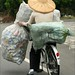farmer carrying sacks of empty cans on a bike 1
