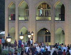 Iranian people relax walking by summer royal palace at dusk, Tabriz, Iran