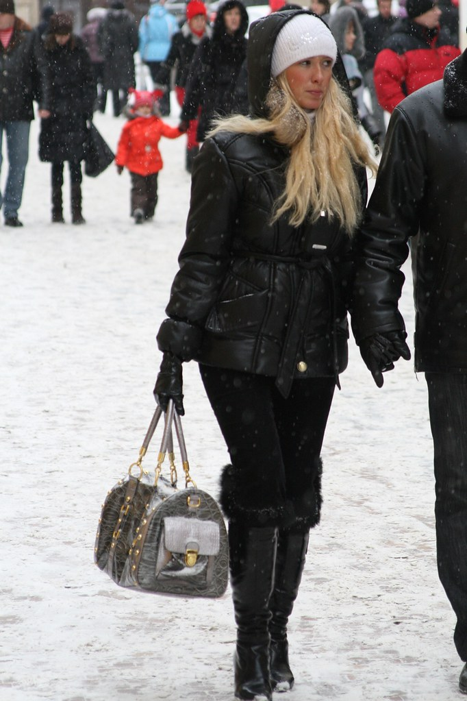 Sexy blonde Russian lady in winter Prague, in high shiny leather boots, leather gloves and black down jacket hood up