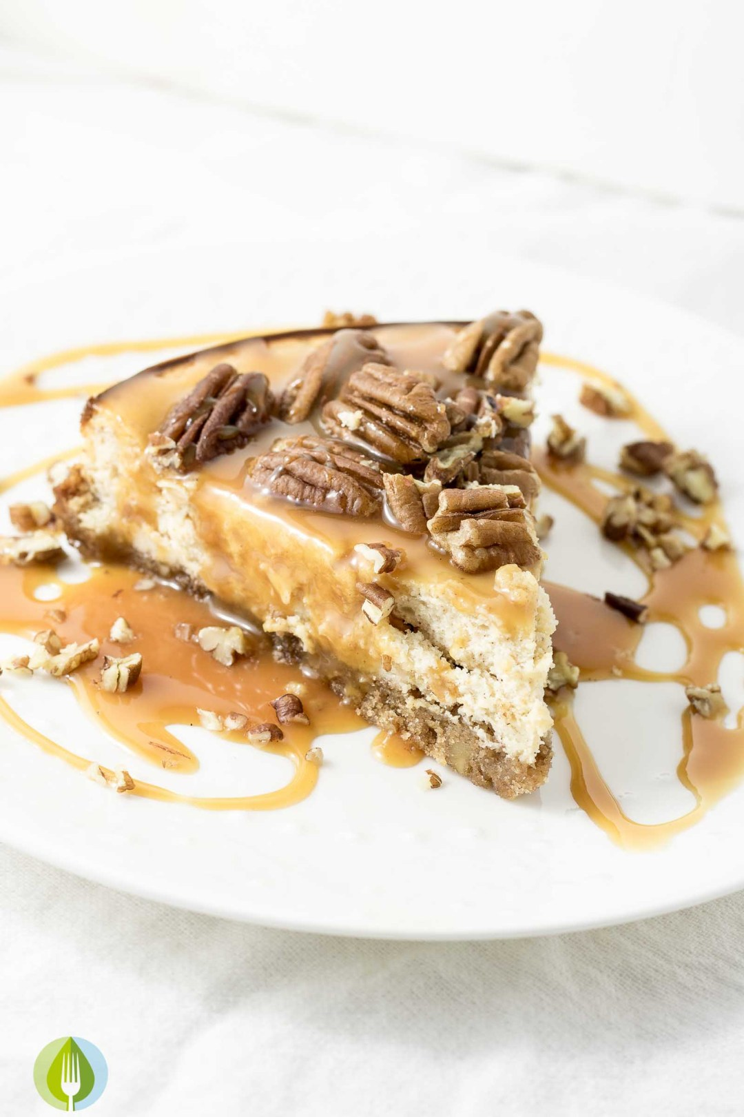 Spiced Whisky Pecan Pie Cheesecake - one slice on a plate with caramel sauce and pecans