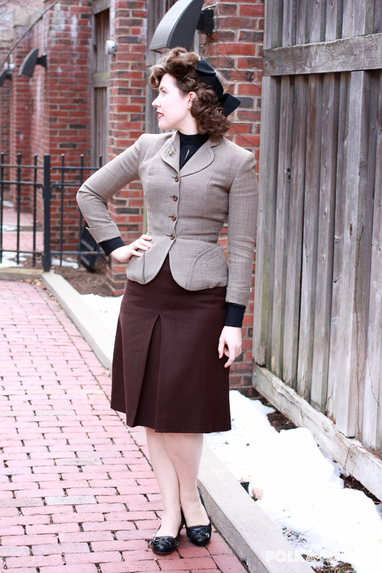 1940s cold weather style with a brown mismatched suit, black accessories, fur tilt hat, and rhinestone spider pin
