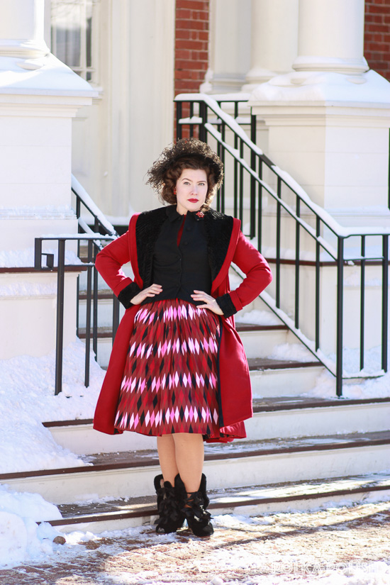Hell Bunny Vivien coat in red paired with a vintage feathered hat, full harlequin print Pin Up Girl Clothing Jenny skirt, black jacket and Royal Vintage Victoria boots