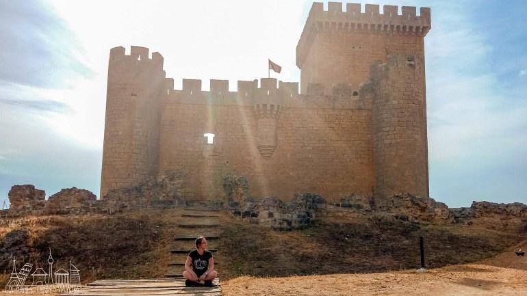 Marina, sentada frente a un castillo con la torre del homenaje a la derecha.