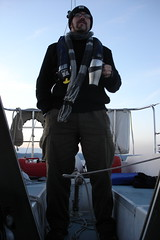 tiller lashed on a reach, steering with body weight, warm beverage in hand