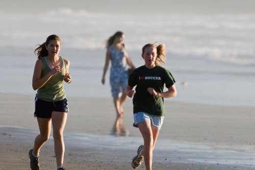 Two female girls jogging on the sand beach in ...