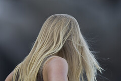 Blond long-haired young lady woman watching th...