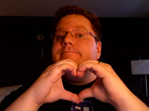 Kevin Lawver making a heart with his hands in a very cheesy self-portrait photo.