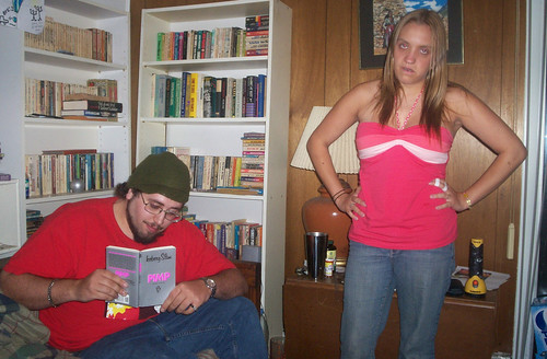 20070615 - Nate's going away party - (by Erin) - Nate (sitting, reading book), Erin (looking mad) - 559154575_f6ff2e766b_b