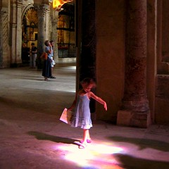 Little girl playing in the stained glass sunlight beam at the Mezquita in Cordoba, Spain
