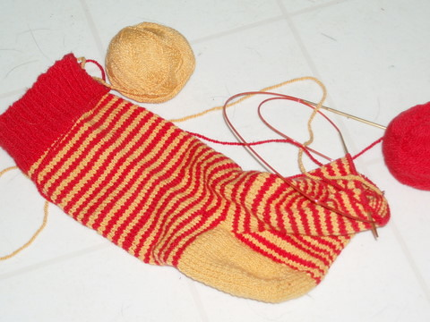 Red and Gold cotton lycra handknit sock almost finished with two balls yarn sitting on the floor