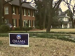 Yard sign in front of a fancy house.