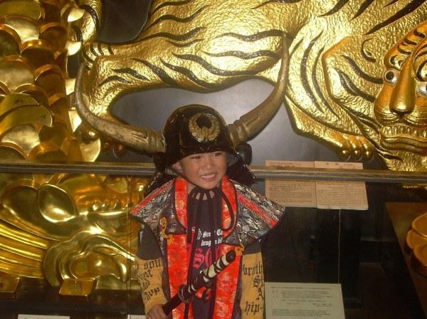 El niño feliz vestido de samurai en el Castillo de Osaka-jo