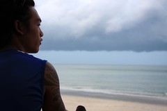 a Thai beach boy looks out to sea on Koh Phangan