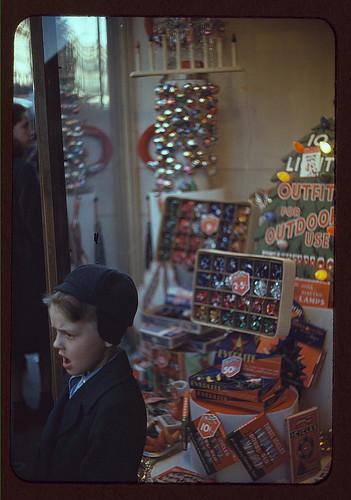 Boy beside store window display of Christmas ornaments