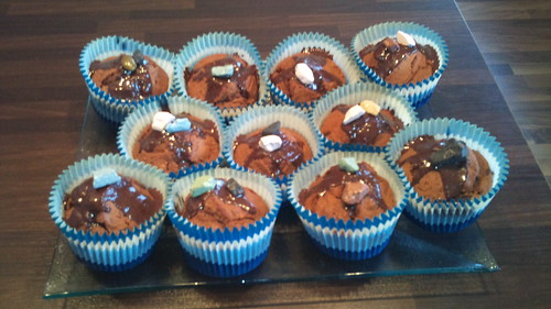 Chocolate muffins with hazelnuts and chocolate pebbles on top.