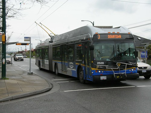 Articulated trolleybus whizzes by a bump out stop