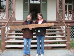 Great-great-great granddaughters of Cottage architect John Skirving, hold a board, signed by their ancestor, which was found in the Cottage during restoration.
