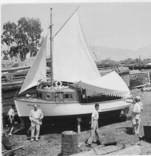 At the Perama slip, a sail fitter is making final Jib adjustments while another sail-maker is trimming the sun awning in the cockpit. On left, in front of the SAMIOPOULA boat name is the prowd owner, Emmanuel Riginos, while his brother George is at the stern (jacket in arm).