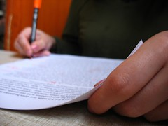 a person writing with a pen and paper