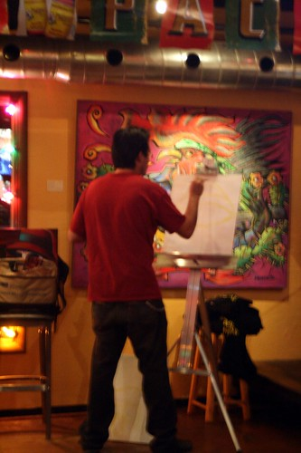 Dude painting in a bar.