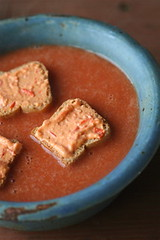 Tomato soup garnished with toasts with peppadew-goat cheese spread